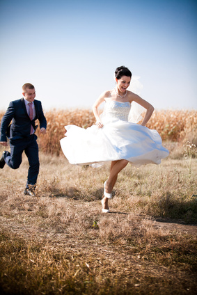 newly married couple chasing each other in field