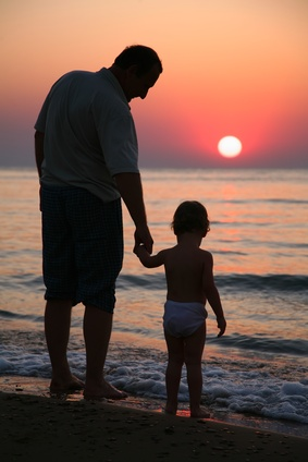 Grandfather with granddaughter on sunset at sea