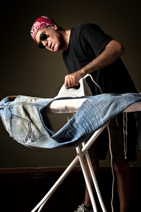 Man ironing a pair of jeans
