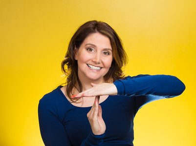 Closeup portrait, young, happy, smiling woman showing time out gesture with hands, isolated yellow background. Positive human emotions, facial expressions, feelings, body language, reaction, attitude